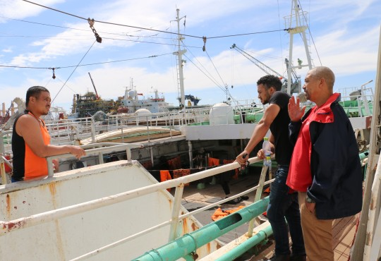 Dane Duplessis (right) and Cassiem Augustus (far right), advise a fisherman (left) at the Cape Town Port
